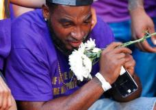 FILE-In this Sunday, Aug. 13, 2017 file photo, Marcus Martin pauses during a vigil, held for the victims of an attack on Saturday in Charlottesville, Va.  James Alex Fields Jr. plowed a car into a crowd of people protesting a white supremacist rally on Saturday, injuring over a dozen people including Martin.   (AP Photo/Steve Helber, File)