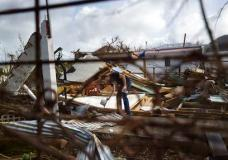 Lex Kools leaves food and water for his neighbors' dogs in the Cole Bay community, in the aftermath of Hurricane Irma, in St. Martin, Tuesday, Sept. 12, 2017. Hundreds of people across an island shared by Dutch St. Martin and French St. Martin are trying to rebuild the lives they had before it was pummeled by a Category 5 storm. (AP Photo/Carlos Giusti)
