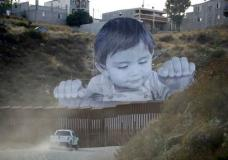HOLD FOR STORY A Border Patrol vehicle drives in front of a mural in Tecate, Mexico, just beyond a border structure Friday, Sept. 8, 2017, in Tecate, Calif. A French artist aiming to prompt discussions about immigration erected a 65-foot-tall cut-out photo of a Mexican boy, pasting it to scaffolding built in Mexico. The image overlooks a section of wall on the California border and will be there for a month. (AP Photo/Gregory Bull)