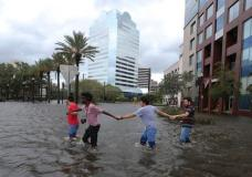 Four people link arms as they explore the flooded Jacksonville Landing in the wake Hurricane Irma on Monday, Sept. 11, 2017, in Jacksonville, Fla. (AP Photo/John Bazemore)