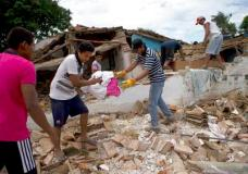 Men pass out household goods salvaged from a home destroyed in Thursday's magnitude 8.1 earthquake, in Union Hidalgo, Oaxaca state, Mexico, Sunday, Sept. 10, 2017. Mexico's government is distributing food to jittery survivors of an earthquake while residents have continued to sleep outside, fearful of more collapses and aftershocks. (AP Photo/Rebecca Blackwell)