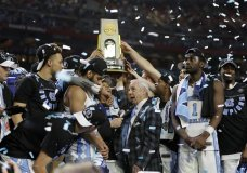 """FILE - In this April 3, 2017, file photo, North Carolina head coach Roy Williams is interviewed as his team celebrate after the finals of the Final Four NCAA college basketball tournament against Gonzaga in Glendale, Ariz. North Carolina's national championship men's basketball team will not visit the White House because of a scheduling conflict. Team spokesman Steve Kirschner said Saturday, Sept. 23, 2017, that Hall of Fame coach Roy Williams and the players were willing to go, and the university and White House tried """"eight or nine"""" dates but none worked. (AP Photo/Mark Humphrey, File)"""