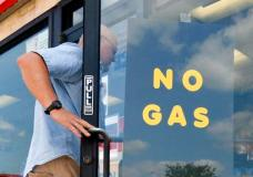 """A customer walks into an Exxon filling station and convenience store location where a sign on the door reads, """"No Gas,"""" Thursday, Aug. 31, 2017, in Bedford, Texas. (AP Photo/Tony Gutierrez)"""
