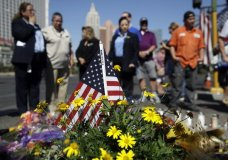 People pause at a memorial for the victims of a mass shooting in Las Vegas, Wednesday, Oct. 4, 2017, in Las Vegas. A gunman opened fire on an outdoor music concert on Sunday killing dozens and injuring hundreds. (AP Photo/John Locher)