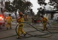 Santa Rosa firefighters carry hose as they battle hotspots in the Coffey Park area of Santa Rosa, Calif., on Tuesday, Oct. 10, 2017. (AP Photo/Ben Margot)