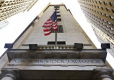 FILE - In this Friday, Nov. 13, 2015, file photo, the American flag flies above the Wall Street entrance to the New York Stock Exchange. U.S. stocks open slightly higher Monday, Oct. 23, 2017, as Seagate and other technology companies rise. The gains are limited as industrial companies and banks take modest losses. Stocks have risen for six consecutive weeks and are trading at record highs. (AP Photo/Richard Drew, File)