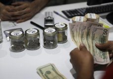 FILE - In this July 1, 2017 file photo, a person buys marijuana at the Essence cannabis dispensary in Las Vegas. The Las Vegas Sun reports more than 40 dispensaries in the Las Vegas area will offer Black Friday discounts on marijuana flower products, edibles such as chocolates, and concentrates. (AP Photo/John Locher, File)