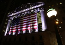 FILE - In this Friday, Feb. 17, 2017, file photo, an American flag hangs on the front of the New York Stock Exchange on an evening in New York. World stock markets mostly fell Tuesday, Dec. 5, 2017, as investors digested the possible impact of the U.S. tax legislation and the stalled Brexit negotiations. (AP Photo/Peter Morgan, File)