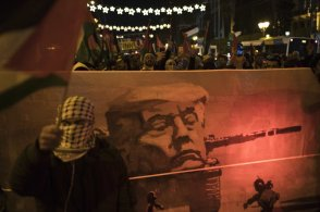 Palestinians hold a placard with the picture of U.S. President Donald Trump during a protest in Athens, on Friday, Dec 8, 2017. Several hundred Palestinians living in Greece, backed by Greek leftist demonstrators, protested the U.S. decision to recognize Jerusalem as the capital of Israel and move its embassy to the contested city. (AP Photo/Petros Giannakouris)