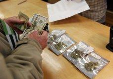 A customer purchases marijuana at Harborside marijuana dispensary, Monday, Jan. 1, 2018, in Oakland, Calif. Starting New Year's Day, recreational marijuana can be sold legally in California. (AP Photo/Mathew Sumner)