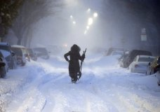 A woman walks down snow-covered Maverick Street in the East Boston neighborhood of Boston, Thursday, Jan. 4, 2018, as a huge winter storm roared up the East Coast with hurricane-force winds, heavy snow and coastal flooding. (AP Photo/Michael Dwyer)