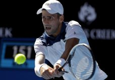 Serbia's Novak Djokovic makes a backhand return to United States' Donald Young during their first round match at the Australian Open tennis championships in Melbourne, Australia, Tuesday, Jan. 16, 2018. (AP Photo/Dita Alangkara )