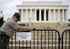 """FILE - In this Oct. 1, 2013, file photo, A U.S. Park Police officer watches at left as a National Park Service employee posts a sign on a barricade closing access to the Lincoln Memorial in Washington. The world won't end if a dysfunctional Washington can't find a way to pass a funding bill before this weekend. That's the truth about a government """"shutdown."""" The government doesn't shut down. It's a crummy way to run a government, sure, but Social Security checks will still go out. Troops will remain at their posts. Doctors and hospitals will get their Medicare and Medicaid reimbursements. In fact, virtually every essential government agency, like the FBI, the Border Patrol and the Coast Guard, will remain open. Transportation Security Administration officers will continue to man airport checkpoints.(AP Photo/Carolyn Kaster, File)"""
