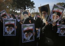 In this photo provided by Tasnim News Agency, women hold posters showing portraits of late Iranian revolutionary founder Ayatollah Khomeini, and Supreme Leader Ayatollah Ali Khamenei during a pro-government rally in the holy city of Qom, Iran, Wednesday, Jan. 3, 2018. Tens of thousands of Iranians took part in pro-government demonstrations in several cities across the country on Wednesday, Iranian state media reported, a move apparently seeking to calm nerves after a week of protests and unrest that have killed at least 21 people. (Mohammad Ali Marizad/Tasnim News Agency via AP)