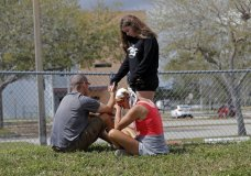A family prays outside Marjory Stoneman Douglas High School in Parkland, Fla., Sunday, Feb. 18, 2018. Authorities opened the streets around the school, which had been closed since a mass shooting on Wednesday. Nikolas Cruz, a former student, was charged with 17 counts of premeditated murder. (AP Photo/Gerald Herbert)