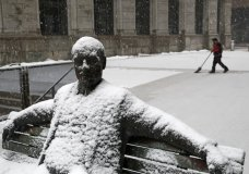 Snow sticks to a statue of a man sitting on a park bench as a worker shovels a light snowfall Wednesday, March 21, 2018, in Baltimore. A spring nor'easter targeted the Northeast on Wednesday with strong winds and a foot or more of snow expected in some parts of the region. (AP Photo/Patrick Semansky)