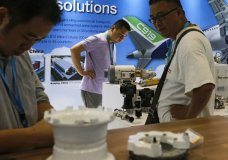 """In this Sept. 20, 2017, photo, visitors look at airplane component parts on display at Aviation Expo China in Beijing. China On Wednesday, April 4, 2018 vowed to take measures of the """"same strength"""" in response to a proposed U.S. tariff hike on $50 billion worth of Chinese goods in a spiraling dispute over technology policy that has fueled fears it might set back a global economic recovery. The Commerce Ministry said it would immediately challenge the U.S. move in the World Trade Organization. (AP Photo/Andy Wong)"""