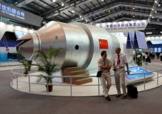 FILE - In this Nov. 16, 2010 file photo, visitors sit beside a model of China's Tiangong-1 space station at the 8th China International Aviation and Aerospace Exhibition in Zhuhai in southern China's Guangdong Province. China's defunct Tiangong 1 space station is expected to re-enter Earth's atmosphere within the next day. The European Space Agency forecast Sunday April 1, 2018 the station will re-enter sometime between Sunday night and early Monday morning GMT. (AP Photo/Kin Cheung, File)