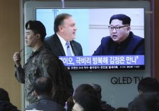 """A South Korean army soldier passes by a TV screen showing file footage of CIA Director Mike Pompeo, left, and North Korean leader Kim Jong Un during a news program at the Seoul Railway Station in Seoul, South Korea, Wednesday, April 18, 2018. Pompeo recently traveled to North Korea to meet with leader Kim Jong Un, a highly unusual, secret visit undertaken as the enemy nations prepare for a meeting between President Donald Trump and North Korean leader Kim Jong Un. The signs read: """" Mike Pompeo meets with Kim Jong Un."""" (AP Photo/Ahn Young-joon)"""