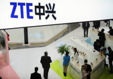 FILE - In this Feb. 26, 2014, file photo, people gather at the ZTE booth at the Mobile World Congress, the world's largest mobile phone trade show in Barcelona, Spain. Chinese telecommunications company ZTE has halted its main operations after U.S. authorities cut off its access to American suppliers as President Donald Trump steps up pressure over trade and technology issues with Beijing. (AP Photo/Manu Fernandez, File)