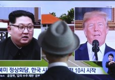 """A man watches a TV screen showing file footage of U.S. President Donald Trump, right, and North Korean leader Kim Jong Un during a news program at the Seoul Railway Station in Seoul, South Korea, Monday, June 11, 2018. Final preparations are underway in Singapore for Tuesday's historic summit between President Trump and North Korean leader Kim, including a plan for the leaders to kick things off by meeting with only their translators present, a U.S. official said. The signs read: """" Summit between the United States and North Korea."""" (AP Photo/Ahn Young-joon)"""