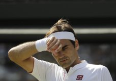 Switzerland's Roger Federer wipes his forehead during the fifth set of his men's quarterfinals match against Kevin Anderson of South Africa at the Wimbledon Tennis Championships, in London, Wednesday July 11, 2018. (AP Photo/Ben Curtis)