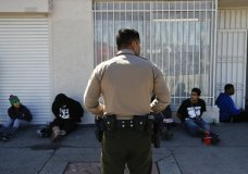 In this March 15, 2018 photo, a Los Angeles County Sheriff's deputy keeps watch on a group of people apprehended at an illegal marijuana dispensary in Compton, Calif. The number of outlaw dispensaries in the county greatly outnumbers the about 150 licensed storefront retailers. (AP Photo/Jae C. Hong)
