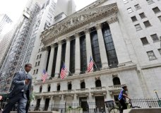 FILE- In this Oct. 24, 2017, file photo, people pass the New York Stock Exchange. The U.S. stock market opens at 9:30 a.m. EDT on Friday, July 20, 2018. (AP Photo/Richard Drew, File)