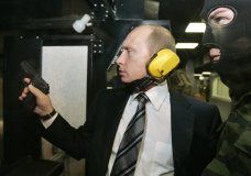 FILE In this file photo taken on Wednesday, Nov. 8, 2006, President Vladimir Putin wears headphones as he tests a pistol in a shooting range as he visits the Defense Ministry's Main Intelligence Directorate in Moscow, Russia. The Justice Department has announced charges against 12 Russian intelligence officers for hacking offenses during the 2016 presidential election, it was announced on Friday, July 13, 2018. (Dmitry Astakhov, Sputnik, Kremlin Pool Photo via AP)