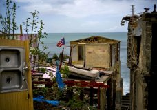 FILE - In this Oct. 5, 2017 file photo, a Puerto Rican national flag is mounted on debris of a damaged home in the aftermath of Hurricane Maria in the seaside slum La Perla, San Juan, Puerto Rico. An independent investigation ordered by Puerto Rico's government estimates that nearly 3,000 people died as a result of Hurricane Maria. The findings issued Tuesday, Aug. 28, 2018, by the Milken Institute School of Public Health at George Washington University contrast sharply with the official death toll of 64. (AP Photo/Ramon Espinosa)