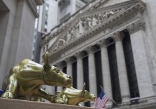 """FILE- In this April 24, 2018, file photo replicas of Arturo Di Modica's """"Charging Bull"""" are for sale on a street vendor's table outside the New York Stock Exchange in New York. The U.S. stock market opens at 9:30 a.m. EDT on Friday, Aug 17. (AP Photo/Mary Altaffer, File)"""