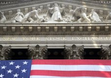 FILE- In this July 6, 2015, file photo, an American flag is draped on the exterior of the New York Stock Exchange. The U.S. stock market opens at 9:30 a.m. EDT on Wednesday, Aug. 22, 2018. (AP Photo/Mark Lennihan, File)