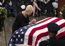 Cindy McCain, wife of Sen. John McCain, R-Ariz., leans over his flag-draped casket in the U.S. Capitol rotunda during a farewell ceremony, Friday, Aug. 31, 2018, in Washington. The six-term Republican senator, who lived and worked in the nation's capital over four decades, is lying in state under the U.S. Capitol rotunda for a ceremony and public visitation. (AP Photo/J. Scott Applewhite)