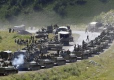 """FILE In this file photo taken on Saturday, Aug. 9, 2008, A column of Russian armoured vehicles seen on their way to the South Ossetian capital Tskhinvali somewhere in the Georgian breakaway region, South Ossetia, Georgia. The Russian military quickly routed the Georgian army during the August 2008 war. Russia's Prime Minister Dmitry Medvedev in an interview broadcast by Russian state television Tuesday Aug. 7, 2018, on the 10th anniversary of the Russia-Georgia war, issued a stern warning that incorporating Georgia into NATO could trigger a new """"horrible"""" conflict.(AP Photo/Musa Sadulayev, File)"""