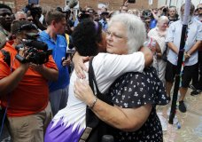 "Susan Bro, mother of Heather Heyer who was killed during last year's Unite the Right rally, embraces supporters after laying flowers at the spot her daughter was killed in Charlottesville, Va., Sunday, Aug. 12, 2018. Bro said there's still ""so much healing to do."" She said the city and the country have a ""huge racial problem"" and that if it's not fixed, ""we'll be right back here in no time."" (AP Photo/Steve Helber)"