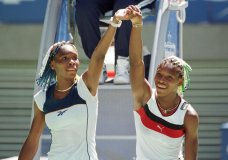 FILE - In this Jan. 21, 1998, file photo, Venus Williams, left, and sister Serena raise their arms after their center court match at the Australian Open Tennis Championships in Melbourne, Australia. Venus won the match 7-6, 6-1. Back when Serena Williams, then 16, and Venus Williams, then 17, played each other on tour for the very first time in January 1998, no one possibly could have known it would signal the start of a series that would last for two decades. (AP Photo/Rick Stevens, File)