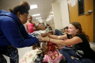 CORRECTS NAME OF HURRICANE TO MICHAEL FROM MATTHEW - Mokeyonia Bell takes her child, Jerah'monie Anthony Bell, 2 months, from godmother Ashley Fillingim, at an evacuation shelter set up at Rutherford High School, in advance of Hurricane Michael, which is expected to make landfall today, in Panama City Beach, Fla., Wednesday, Oct. 10, 2018. (AP Photo/Gerald Herbert)