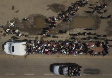 Migrants climb on the trailer of a truck as others wait in a line for a ride on the road that connects Tapanatepec with Niltepec, Mexico, as a caravan of Central Americans continues its slow march toward the U.S. border, Monday, Oct. 29, 2018. Thousands of migrants traveling together for safety resumed their journey after taking a rest day Sunday, while hundreds more migrants were pushing for entry to Mexico. (AP Photo/Rodrigo Abd)