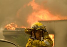 A firefighter keeps watch as the wildfire burns a home near Malibu Lake in Malibu, Calif., Friday, Nov. 9, 2018. About two-thirds of the city of Malibu was ordered evacuated early Friday as a ferocious wildfire roared toward the beachside community that is home to about 13,000 residents, some of them Hollywood celebrities. (AP Photo/Ringo H.W. Chiu)