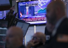 Traders at the New York Stock Exchange listen as Federal Reserve Chair Jerome Powell is
