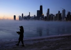 A person walks along the lakeshore, Wednesday, Jan. 30, 2019, in Chicago. A deadly arctic deep freeze enveloped the Midwest with record-breaking temperatures on Wednesday, triggering widespread closures of schools and businesses, and prompting the U.S. Postal Service to take the rare step of suspending mail delivery to a wide swath of the region. (AP Photo/Kiichiro Sato)
