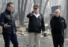 "FILE - In this Nov. 17, 2018, file photo, President Donald Trump talks with then Gov.-elect Gavin Newsom, left, and as California Gov. Jerry Brown listens during a visit to a neighborhood impacted by the wildfires in Paradise, Calif. California Gov. Gavin Newsom says the Trump administration is engaging in ""political retribution"" by trying to take back $3.5 billion granted for the state's high-speed rail project. The Democratic governor says President Donald Trump is reacting to California suing over Trump's emergency declaration to pay for a wall along the U.S.-Mexico border. (AP Photo/Evan Vucci, File)"