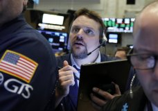 FILE- In this March 12, 2019, file photo, trader Michael Milano works on the floor of the New York Stock Exchange. The U.S. stock market opens at 9:30 a.m. EDT on Monday, March 18. (AP Photo/Richard Drew, File)