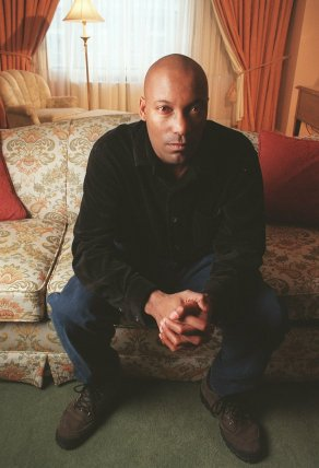 """FILE - This Feb. 9, 1997 file photo shows film director John Singleton posing in New York to promote his film """"Rosewood."""" The family for Singleton says the filmmaker will be taken off life support Monday, April 29, 2019, after suffering a stroke almost two weeks ago. In a statement Monday, Singleton's family said it was """"an agonizing decision, one that our family made over a number of days with the careful counsel of John's doctors."""" (AP Photo/Todd Plitt)"""