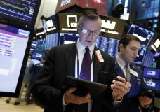 FILE- In this April 2, 2019, file photo traders Neal Catania, left, and Benjamin Tuchman work on the floor of the New York Stock Exchange. Stock markets were subdued Monday, April 8, after trade talks between China and the U.S. wrapped up with officials claiming progress. The price of oil kept rose to its highest level this year on the back of improved U.S. economic data. (AP Photo/Richard Drew, File)