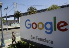 FILE - In this May 1, 2019, file photo a man walks past a Google sign outside with a span of the Bay Bridge at rear in San Francisco. Google is acquiring data analytics firm Looker for $2.6 billion cash in an effort to expand its Google Cloud business. The company says Looker will give its cloud-computing customers more ways to use their data. (AP Photo/Jeff Chiu, File)