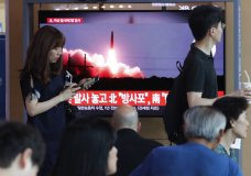 """People watch a TV showing a file image of North Korea's missile launch during a news program at the Seoul Railway Station in Seoul, South Korea, Tuesday, Aug. 6, 2019. North Korea on Tuesday continued to ramp up its weapons demonstrations by firing unidentified projectiles twice into the sea while lashing out at the United States and South Korea for continuing their joint military exercises that the North says could derail fragile nuclear diplomacy. The sign reads """"North Korea's multiple rocket launchers system."""" (AP Photo/Ahn Young-joon)"""