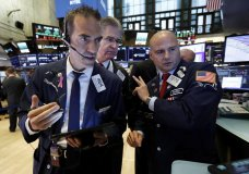 Traders Gregory Rowe, left, and Daniel Kryger, center, work with specialist Mario Picone on the floor of the New York Stock Exchange, Tuesday, Aug. 6, 2019. Stock markets turned higher on Tuesday as China stabilized its currency after allowing it to depreciate against the dollar in response to President Donald Trump's decision to put more tariffs on Chinese goods. (AP Photo/Richard Drew)