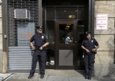 FILE - In this Thursday, June 21, 2018 file photo, police stand outside an office for the Cayuga Centers in the Brooklyn borough of New York. Three of the four incidents involving physical harm to separated immigrant children, outlined in legal filings, involved charges of Cayuga Centers, the largest foster care placement for migrant children. (AP Photo/Richard Drew)