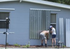 James Wolfe, 72, left, and Elaine Wolfe, 65, install shutters on their home in Vero Beach, Fla, Thursday, Aug. 29, 2019. The U.S. National Hurricane Center says Dorian could hit the Florida coast over the weekend as a major hurricane. (AP Photo/Ellis Rua)